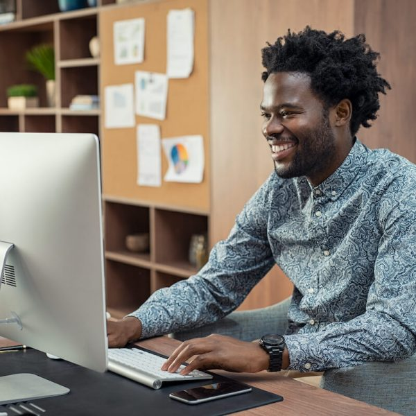 happy-african-businessman-using-computer-HYFSMPN