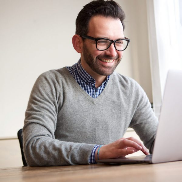 happy-businessman-working-with-laptop-computer-B8TVA6R